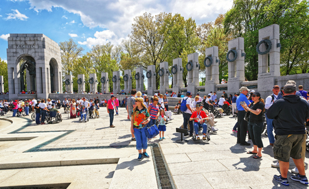 guardians: Washington DC, USA - May 2, 2015: Tourists and War Veterans and guardians of Honor Flight nonprofit organization on National World War Two Memorial, National Mall. Pacific Arch on the left