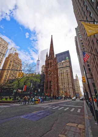 Nueva York, EE.UU. - 24 de abril de 2015: Iglesia de la Trinidad en el Bajo Manhattan y la vista de la calle de la carretera y los turistas, Nueva York, EE.UU.. Se trata de una histórica iglesia parroquial cerca de Wall Street y Broadway. Editorial