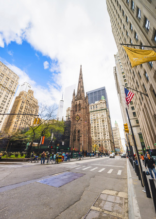 broadway tower: New York, USA - April 24, 2015: Trinity Church in Lower Manhattan and street with traffic and tourists, New York, USA. It is a historic parish church near Wall Street and Broadway.