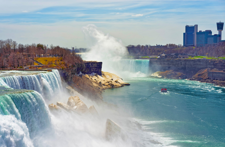 the edge of horseshoe falls: Niagara Falls and a Ferry on Niagara River from Canadian side. A view on American Falls, Bridal Veil Falls, Goat Island, Horseshoe falls and Canada Skyscrapers on the background.