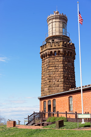 twin house: Light house and an American flag at Sandy Hook. It is called Navesink Twin Lights. Sandy Hook is located in Highlands in Monmouth County of New Jersey, USA Stock Photo
