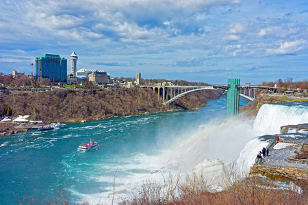 niagara river: Rainbow in Niagara Falls and Rainbow Bridge across the Niagara River Gorge. It is an arch bridge between the United States of America and Canada. Tourists nearby