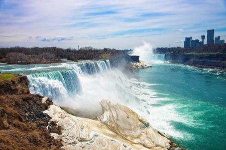 american falls: Niagara Falls from American side and Skyscrapers in Canada. A view on American Falls, Bridal Veil Falls, Goat Island, Horseshoe falls and Canada Skyscrapers on the background.
