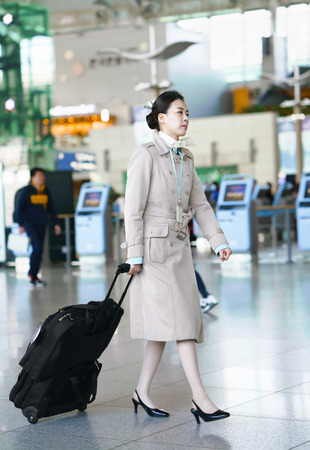 mid air: Incheon, South Korea - February 15, 2016: Asian Korean female air flight hostess at Incheon International airport. It is one of the largest and busiest world airports.