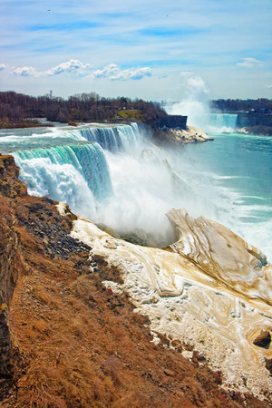 the edge of horseshoe falls: Niagara Falls from the American side. A view from Niagara State Park on American Falls, Bridal Veil Falls, Goat Island and Horseshoe falls on the background.