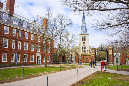 harvard university: Cambridge, USA - April 29, 2015: First Parish Church in Harvard Square and tourists in Harvard Yard in the campus of Harvard University, Massachusetts, MA, USA. The church is built 400 years ago.