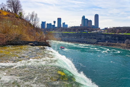 american falls: Niagara Falls, ferry in Niagara River and Skyscrapers from the Canadian side. A view on American Falls Stock Photo