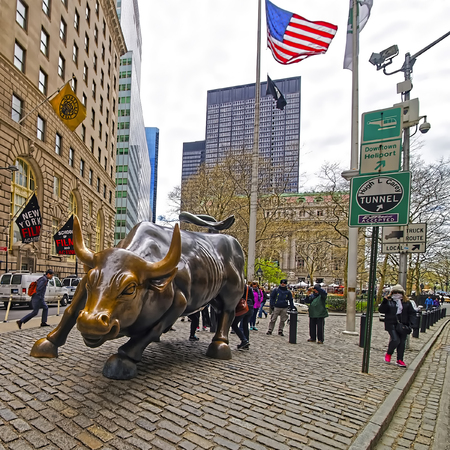 New York, USA - April 24, 2015: Charging Bull at Wall Street in Financial District in Lower Manhattan, New York, USA. Tourists in the street Editorial