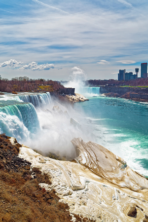 american falls: Niagara Falls from an American side and Skyscrapers in Canada. A view on American Falls, Bridal Veil Falls, Goat Island, Horseshoe falls and Canada Skyscrapers on the background. Stock Photo