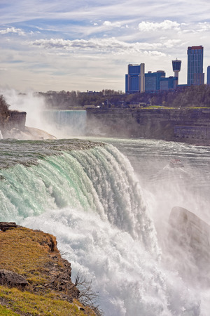 the edge of horseshoe falls: Niagara Falls from the American side and Skyscrapers from the Canadian side. A view on American Falls, Bridal Veil Falls, Horseshoe falls and Canada Skyscrapers on the background. Stock Photo