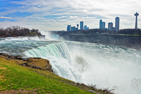 the edge of horseshoe falls: Niagara Falls from the American side and Skyscrapers in Canada. A view on American Falls, Bridal Veil Falls, Goat Island, Horseshoe falls and Canada Skyscrapers on the background.