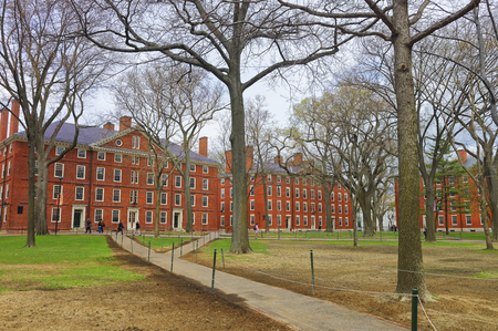 harvard: Cambridge, USA - April 29, 2015: Hollis Hall and Stoughton Hall in Harvard Yard of Harvard University, Massachusetts, MA. They serve as dormitories for Harvard students. Tourists in the street