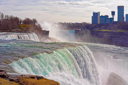 american falls: Niagara Falls from the American side and Skyscrapers from a Canadian side. A view on American Falls, Bridal Veil Falls, Goat Island, Horseshoe falls and Canada Skyscrapers on the background.