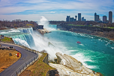 american falls: Niagara Falls and a Ferry on Niagara River from the American side. A view on American Falls, Bridal Veil Falls, Goat Island, Horseshoe falls and Canada Skyscrapers on the background. Stock Photo