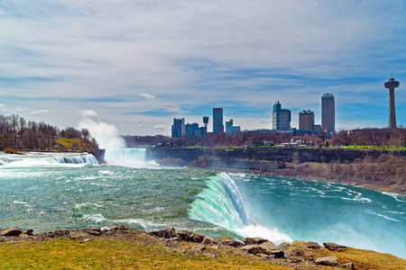 the edge of horseshoe falls: Niagara Falls from the American side and Skyscrapers from Canadian side. A view on American Falls, Bridal Veil Falls, Goat Island, Horseshoe falls and Canada Skyscrapers on the background.