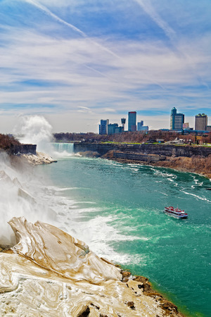 american falls: Niagara Falls and Ferry on Niagara River from American side. A view on American Falls, Horseshoe falls and Skyscrapers in Canada on the background. Stock Photo
