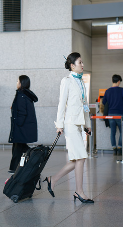 hostess: Incheon, South Korea - February 15, 2016: Asian Korean female air flight attendant in the Incheon international airport. It is one of the largest and busiest world airports