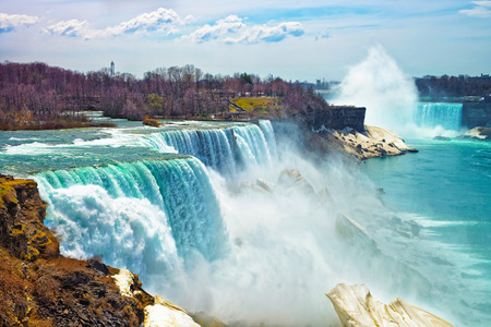 the edge of horseshoe falls: Niagara Falls from the American side in spring. A view from Niagara State Park on American Falls, Bridal Veil Falls, Goat Island and Horseshoe falls on the background.