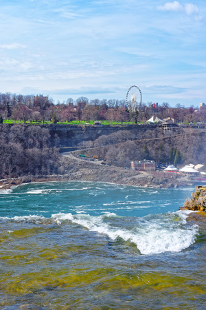 niagara falls city: Niagara Falls in US and View of Ontario in Canada near Niagara River. Niagara River is a border between the United States of America and Canada. Tourists nearby