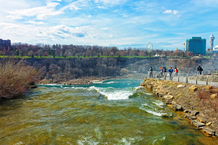 niagara falls city: Niagara Falls in US and View on Ontario in Canada near Niagara River. Niagara River is a border between the United States of America and Canada. Tourists nearby