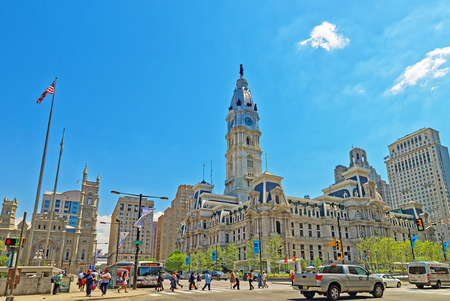 Philadelphia, USA - May 4, 2015: Philadelphia City Hall with William Penn figure atop the Tower. View from the street. Tourists in the street