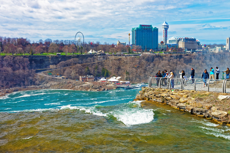 niagara river: Niagara Falls, USA - April 30, 2015: Niagara River and Cityscape of Ontario near Niagara Falls. Niagara River is a border between the United States of America and Canada. Tourists nearby Editorial