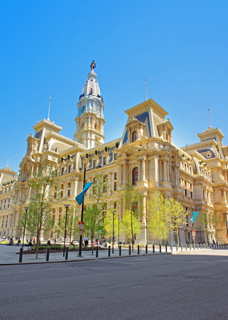 Philadelphia, USA - May 4, 2015: Philadelphia City Hall with William Penn statue atop Tower. View from the street. Tourists in the street