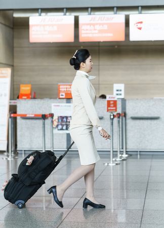 hostess: Incheon, South Korea - February 15, 2016: Asian Korean air flight stewardess on the Incheon International airport. It is one of the largest and busiest world airports.