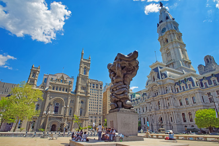 municipal court: Philadelphia, USA - May 4, 2015: Square with Government of the people sculpture and tourists, and Philadelphia City Hall and Church on the background. Pennsylvania, USA. Editorial