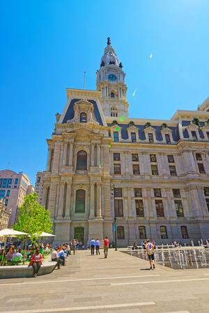 Philadelphia, USA - May 4, 2015: Philadelphia City Hall with fountain on Penn Square. Tourists on the square. Pennsylvania, USA. With special sun flare