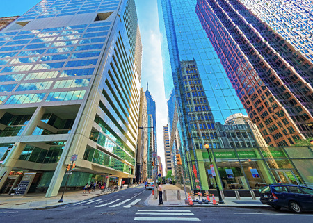 business center: Philadelphia, USA - May 4, 2015: Arch Street view with skyscrapers reflected in glass in the City Center of Philadelphia, Pennsylvania, the USA. It is central business district in Philadelphia. Tourists in the street Editorial