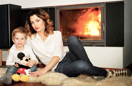Vilnius, Lithuania - January 23, 2016: Beautiful family consisting of mother with ginger hair and a small son sitting on the fur carpet at the fireplace. Fire in the fireplace is burning.