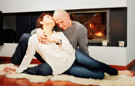 skinhead: Romantic pair of brunette woman and bald headed man sitting with passion on the fur carpet near the fireplace. Fire in the fireplace is burning.