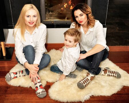 fireplace family: Beautiful family consisting of mother with ginger hair, daughter with blond hair and a son sitting on the fur carpet near fireplace. Fire in the fireplace is burning. Stock Photo