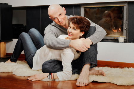 brune: Romantic pair of brunette woman and bald headed man sitting on the fur carpet near a fireplace. Fire in the fireplace is burning.