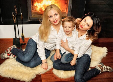ginger hair: Beautiful family consisting of mother with ginger hair, daughter with blond hair and a son sitting on the fur carpet at fireplace. Fire in the fireplace is burning.