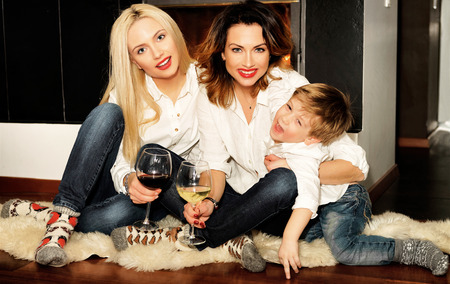 fireplace family: Beautiful family consisting of mother with ginger hair, daughter with blond hair and a son sitting on the fur carpet at the fireplace. Fire in the fireplace is burning. Women holding glasses of wine.