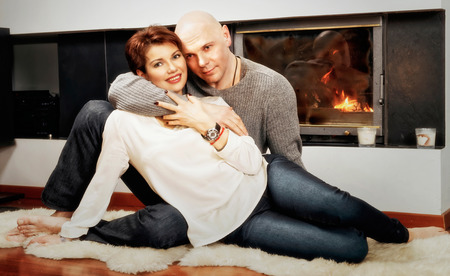 skinhead: Romantic pair of brunette woman and bald headed man sitting on the fur carpet near the fireplace. Fire in the fireplace is burning. Stock Photo