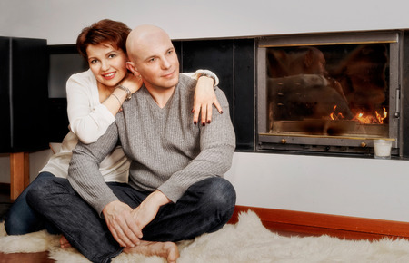 brune: Romantic couple of brunette woman and bald headed man sitting on the fur carpet near the fireplace. Fire in the fireplace is burning.