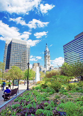 Philadelphia, USA - May 5, 2015: Walkway with Fountain in Love Park and Philadelphia City Hall on the background. Tourists on the walkway. Pennsylvania, USA.