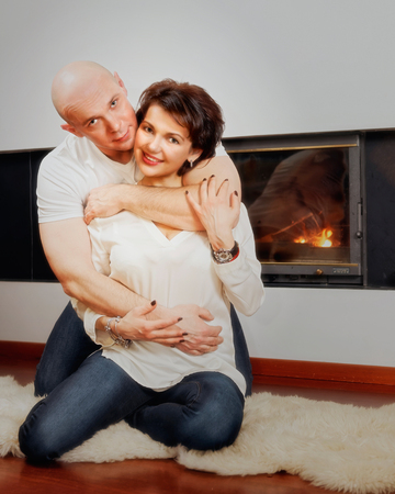 skinhead: Romantic couple of brunette woman and bald headed man sitting on the fur carpet near fireplace. Fire in the fireplace is burning.