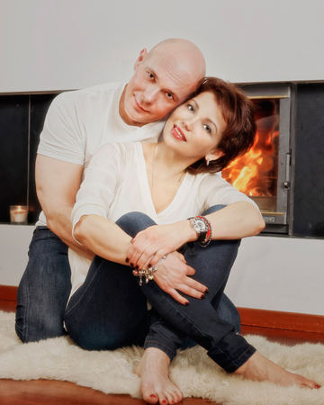 brune: Beautiful couple of brunette woman and bald headed man sitting on the fur carpet near fireplace. Fire in the fireplace is burning. Stock Photo