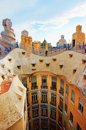 BARCELONA, SPAIN - AUGUST 14, 2011: Roof with chimneys and tourists at Casa Mila building in Barcelona in Spain. Also called as La Pedrera, or Miracle Home, or The Quarry. Designed by Antoni Gaudi