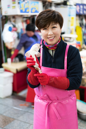 merchant: Busan, South Korea - March, 13, 2016: Asian woman selling a small shark in the fish market in Jagalchi in Busan, South Korea