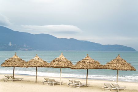 Palm shelters with sunbeds in the China Beach in Da Nang, Vietnam. It is also called NonNuoc Beach. South China Sea and Marble Mountains on the background. Stock Photo
