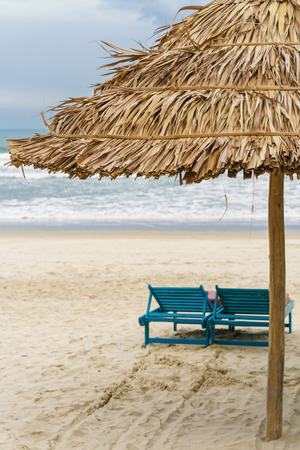 Palm shelter and sunbeds in the China Beach in Da Nang, Vietnam. It is also called Non Nuoc Beach. South China Sea on the background. Stock Photo