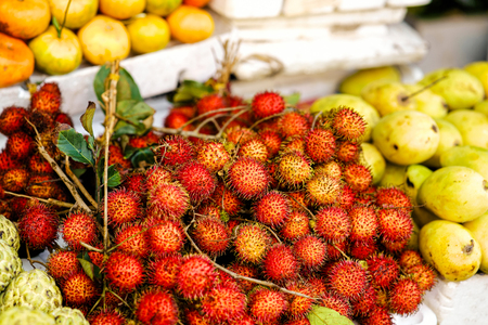 Asian street farmer market selling fresh fruit in Hoi An, Vietnam. Rambutan and mango. Yellow and red colors. Stock Photo