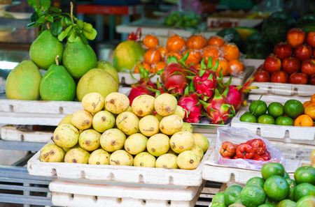 Asian street farmer market selling fresh fruit in Hoi An, Vietnam. Mango, guava and dragon fruit. Yellow, red and green colors. Stock Photo