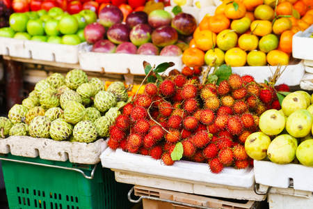 chirimoya: Asian street farmer market selling fresh fruit and berry in Hoi An, Vietnam. Passion fruit, litchi, cherimoya, mango and other. Red, orange and green colors. Stock Photo