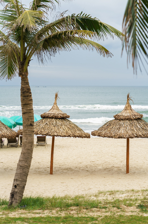 beachfront: Palms shelter and sunbeds in the China Beach in Da Nang, Vietnam. It is also called Non Nuoc Beach. South China Sea on the background.